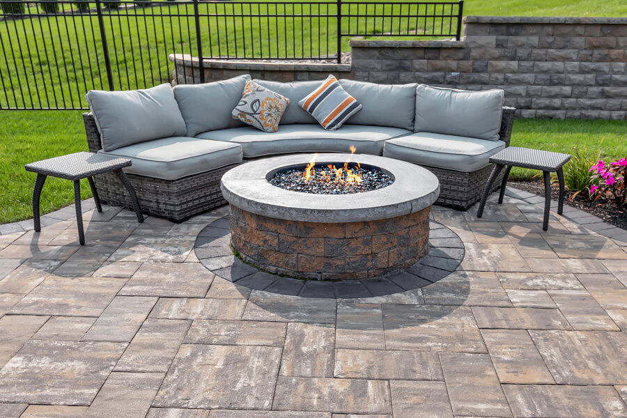 A firepit and a couch in an outdoor lounge area.