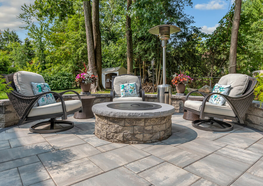 Three chairs and a firepit in an outdoor patio.