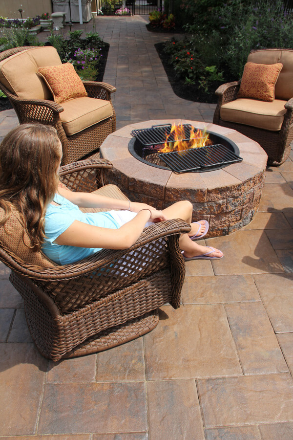 A woman sitting in a chair in front of a firepit.